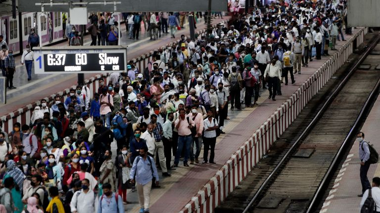 Commuters wait to board a train at Chhatrapati Shivaji Maharaj Terminus the night before a curfew was due to be introduced in Mumbai