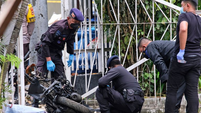 Members of police bomb squad inspect the wreckage of a motorbike used to carry out Sunday...s suicide bomb attack at Sacred Heart of Jesus Cathedral in Makassar, South Sulawesi, Indonesia,  Two attackers believed to be members of a militant network that pledged allegiance to the Islamic State group blew themselves up outside the packed Roman Catholic cathedral during a Palm Sunday Mass on Indonesia...s Sulawesi island, wounding a number of people, police said. (AP Photo/Masyudi S. Firmansyah)