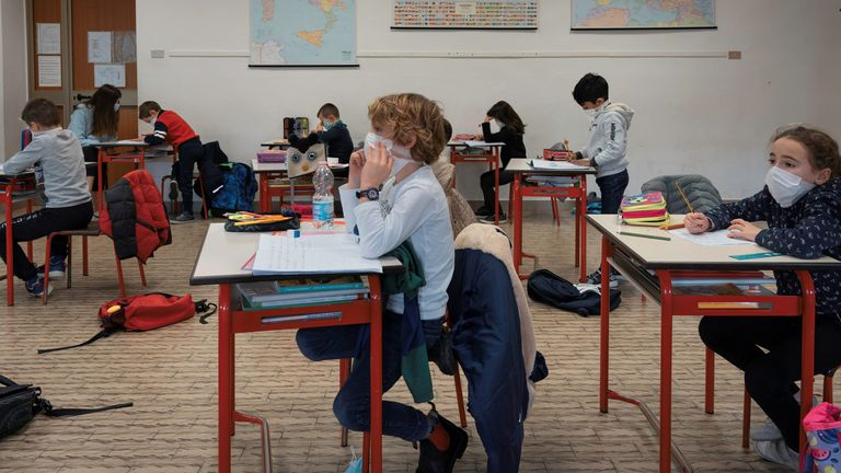 Italian primary school pupils, wearing masks, sit at a distance apart from each other during a lesson as they return to the classroom after the holidays, in Santo Stefano Lodigiano, Italy, January 7, 2021