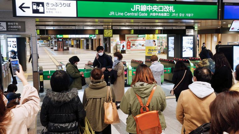 People in Sendai gather in front of a ticket gate at a station as train services are suspended. Pic: AP