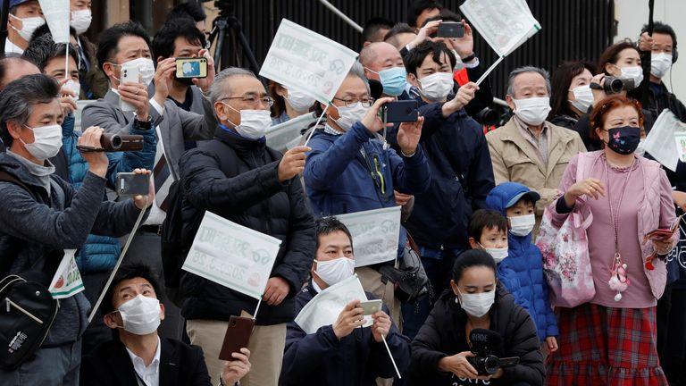 افرادی که ماسک محافظ صورت دارند ، در حال دویدن حامل مشعل از کنار گذشته است