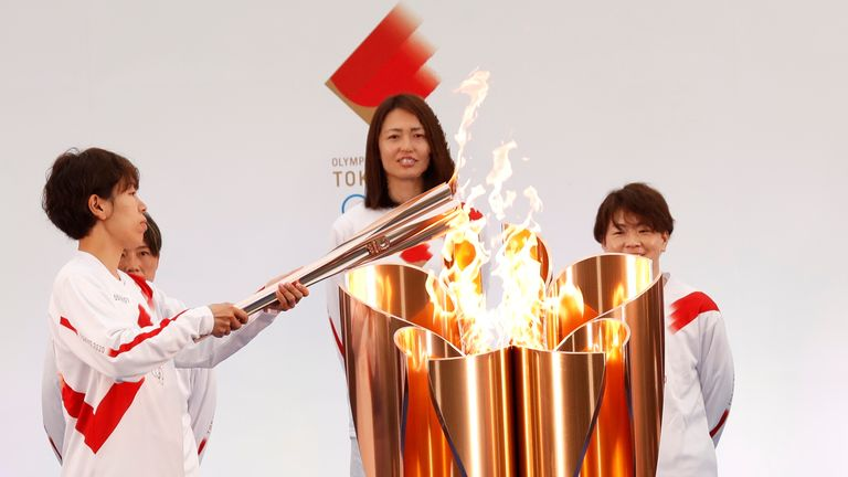 The torch is lit by a member of Japan's women's national soccer team