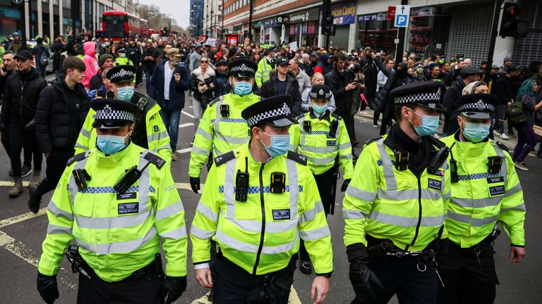 Police officers walk as people attend a protest against the lockdown,