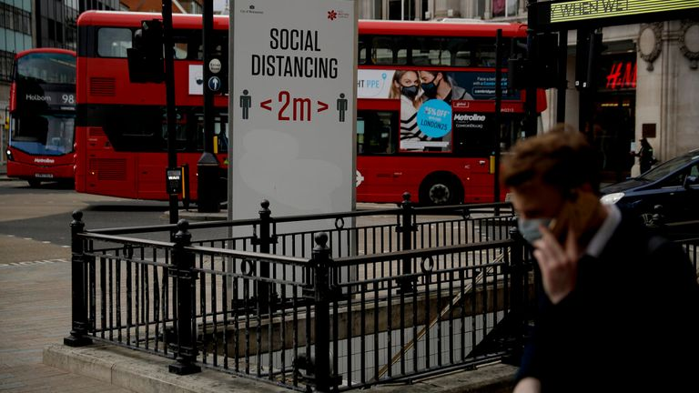 A large social distancing sign is displayed next to an entrance down into Oxford Circus underground train station, in central London, during England's third coronavirus lockdown, Friday, March 26, 2021. The pandemic has battered the British economy, which has suffered its deepest recession in more than 300 years. Pubs, restaurants, theaters, hair salons and all stores selling nonessential items such as books and footwear have spent much of the past year closed. (AP Photo/Matt Dunham)
