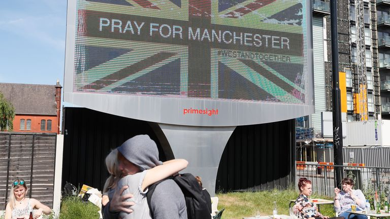 In this Tuesday May 23, 2017 file photo, couple embrace under a billboard in Manchester, England, the day after the suicide attack at an Ariana Grande concert that left more than 20 people dead. Firefighters were not allowed to go to the scene of the Manchester Arena bombing for more than two hours because of confusion about whether an attacker was still on the loose, according to an inquiry into the attack released Tuesday March 27, 2018. (AP Photo/Kirsty Wigglesworth, File)