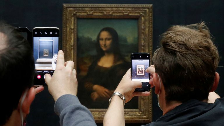 """Visitors take pictures of the painting """"Mona Lisa"""" (La Joconde) by Leonardo da Vinci at the Louvre museum in Paris as the museum reopens its doors to the public after an almost four-month closure due to the coronavirus disease (COVID-19) outbreak in France, July 6, 2020"""