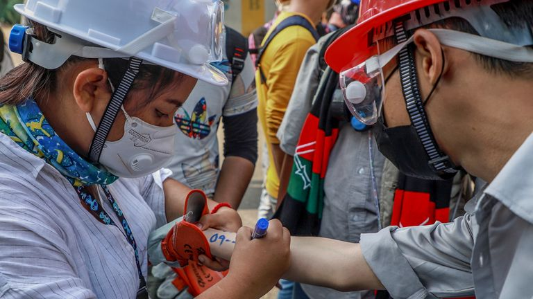 An anti-coup protester writes vital emergency information of another protester on his arm in Yangon, Myanmar Wednesday, March 3, 2021. Demonstrators in Myanmar took to the streets again on Wednesday to protest last month's seizure of power by the military. (AP Photo)