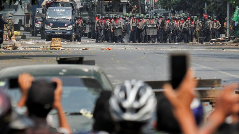 Police stand on a road during an anti-coup protest in Mandalay, Myanmar