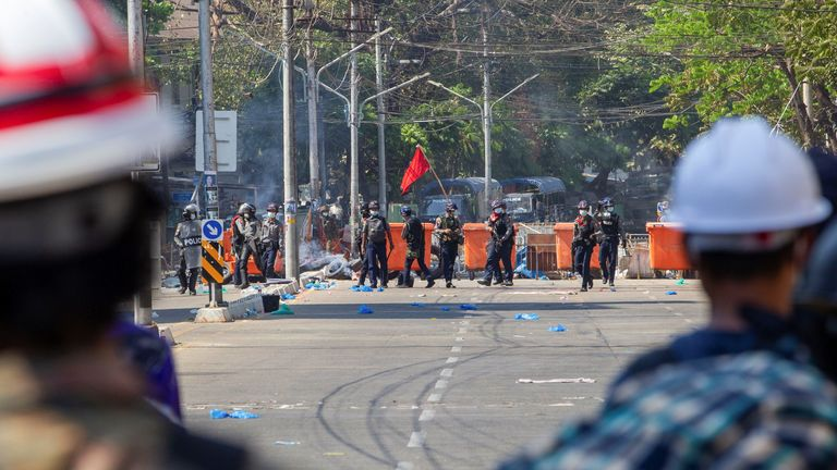 Police are seen in front of a protester barricade in Yangon