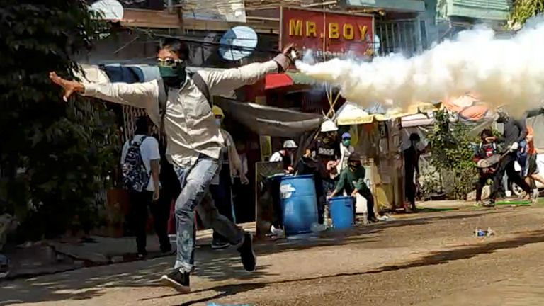 A demonstrator runs with a tear gas canister during a protest in Yangon