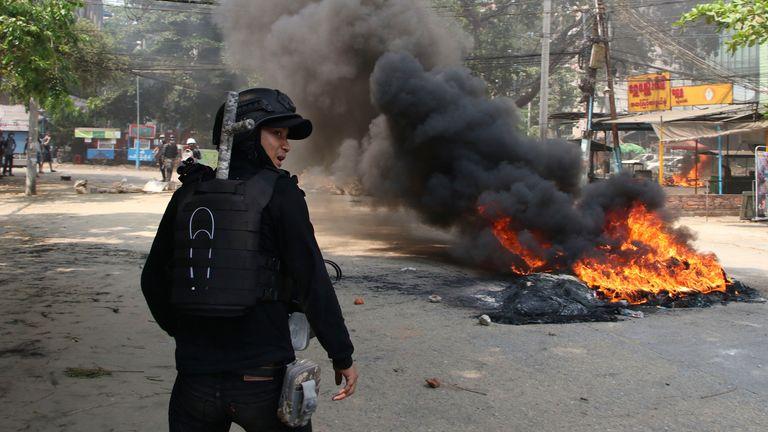 یک معترض ضد کودتا هنگام تظاهرات در شهر دالا ، یانگون ، در نزدیکی آتش ایستاده است.  عکس: AP