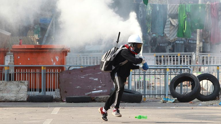 An anti-coup protester sprays a fire extinguisher near a police barricade in Yangon