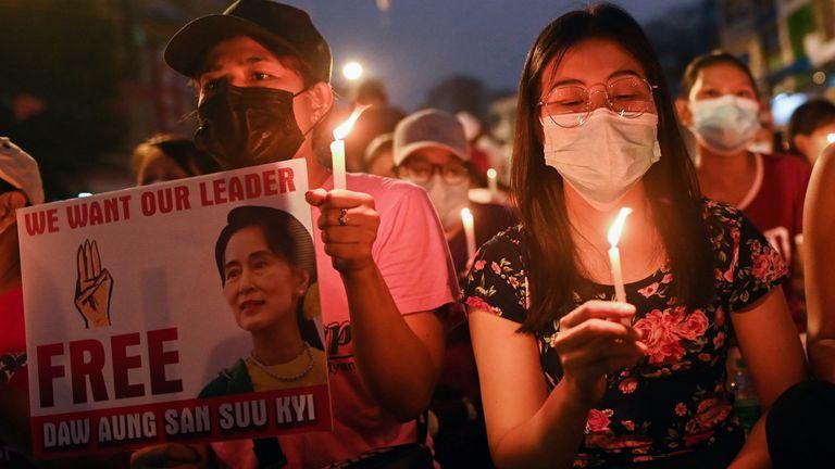 مردم هنگام شرکت در تظاهرات شبانه ضد کودتا در یانگون شمع به دست می گیرند