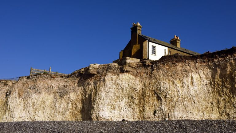 A cottage sits precariously close to the cliff edge. Birling Gap and Crowlink, near Eastbourne in East Sussex, are part of the world famous Seven Sisters chalk cliffs, one of the longest stretches of undeveloped coastline on the south coast. National Trust is warning about the effect unchecked climate change will have on its properties and landscapes Pic: National Trust