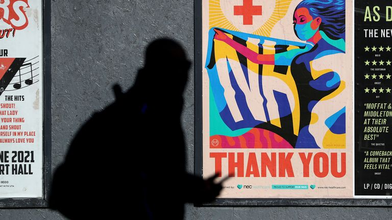 A person walks passed an advertising board in Glasgow showing a Thank You NHS poster, as lockdown measures for mainland Scotland continue. Picture date: Friday March 12, 2021.