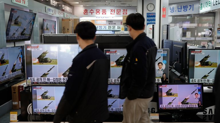 People walk past near TV screens showing a news program reporting about North Korea's missiles with file images at an electronic shop in Seoul, South Korea, Wednesday, March 24, 2021. Pic: AP