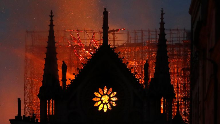 In this April 15, 2019, file photo, flames and smoke rise from Notre Dame Cathedral as it burns in Paris. The cathedral stands crippled, locked in a dangerous web of twisted metal scaffolding one year after a cataclysmic fire gutted its interior, toppled its famous spire and horrified the world. (AP Photo/Thibault Camus, File)