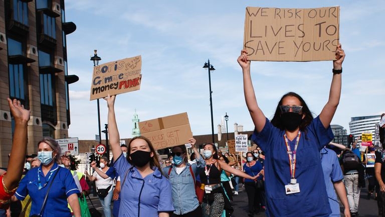 National Health Service (NHS) staff wearing masks are seen protesting their exclusion from a recently-announced public sector pay rise, on Parliament Square. Around 900,000 public sector workers across the UK are set to receive above-inflation pay rise this year as a gratitude gesture from the Treasury for their efforts during the coronavirus pandemic. The pay rise is however exclusive of nurses and other front-line staff owing to a three-year pay deal they negotiated in 2018 which led them to m