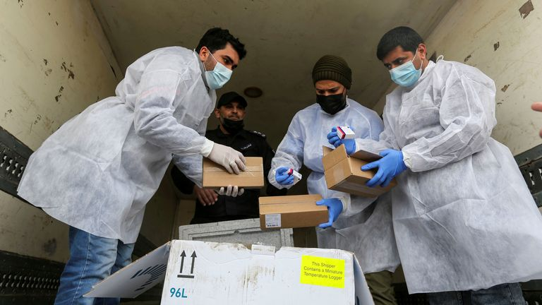 Palestinian workers unload a shipment of vaccines in the Gaza Strip
