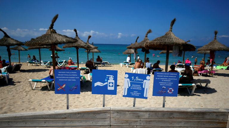 Signs are pictured as people sunbathe and swim on El Arenal beach in Palma de Mallorca (file pic)
