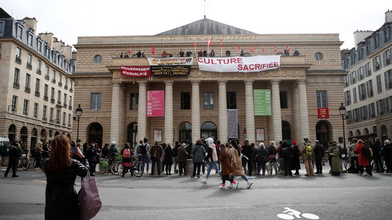 Culture workers and artists hang banners and flags from the balcony of Paris' Theatre de l'Odeon, to protest against the government decision to keep theatres, cinemas, concert halls and museums closed