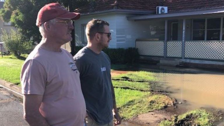 Paul Luckman and Blake Lepaglier survey the flooding damage to their homes