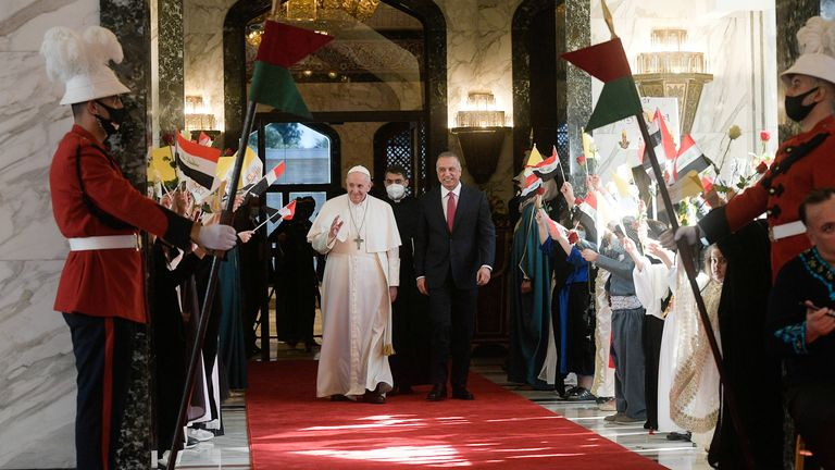 Iraqi Prime Minister Mustafa Al-Kadhimi walks with Pope Francis upon his arrival at Baghdad International Airport