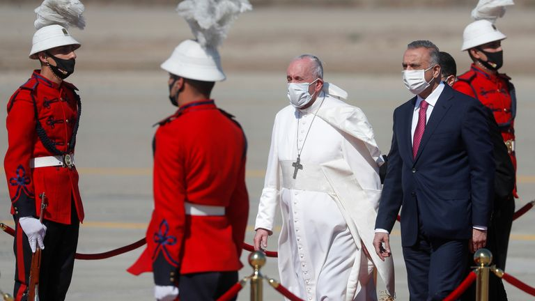Pope Francis is received by Iraqi Prime Minister Mustafa Al-Kadhimi upon disembarking from his plane at Baghdad International Airport to start his historic tour in Baghdad, Iraq, March 5, 2021. REUTERS/Yara Nardi
