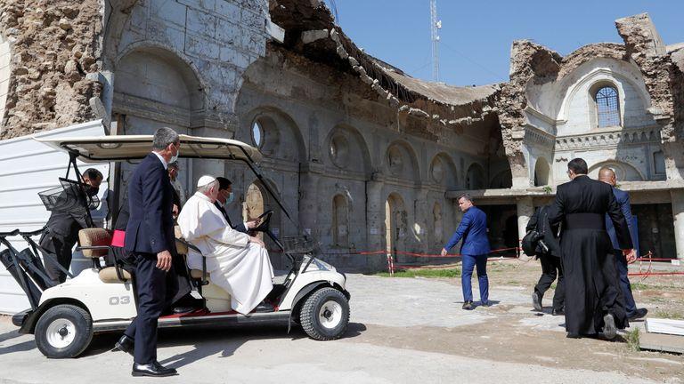 Pope Francis, sitting in a cart, is shown the devastation of the Syriac Catholic Al Tahera church near Hosh al Bieaa Church Square. Pic: AP