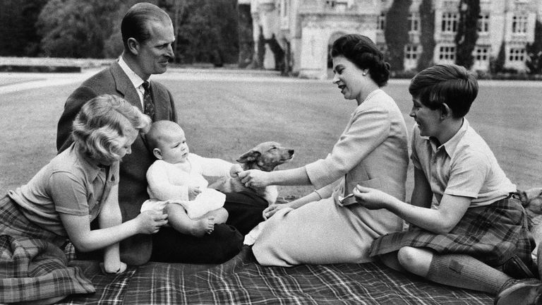 Britain's Royal family sits on blanket on the grounds of Balmoral Castle, Scotland, Sept. 8, 1960, during current holiday. Prince Andrew, in lap of his father, Prince Philip, reaches for trinket presented by his mother, Queen Elizabeth II, Princess Anne and Prince Charles try to catch the baby's attention. (AP Photo)