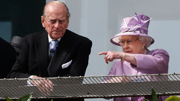 Britain's Queen Elizabeth II points out something to Prince Philip as they watches the Epsom Derby from the balcony at Epsom racecourse, England, Saturday, June 7, 2014. (AP Photo/Sang Tan)