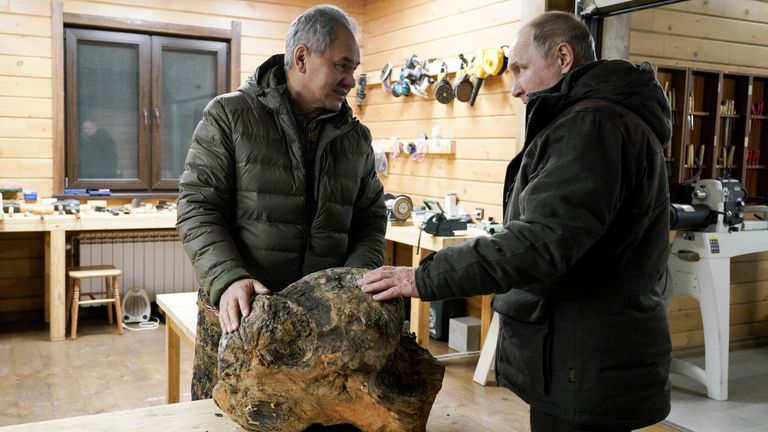 Russia Defense Minister Sergei Shoigu, left, and Russian President Vladimir Putin talk to each other and look at a piece of wood for crafting at Sergei Shoigu's workroom in a taiga forest in Russia's Siberian region in Russia.