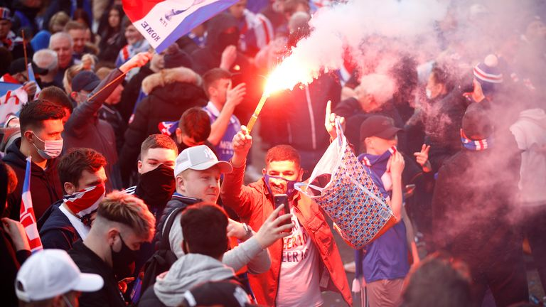 A Rangers fan celebrates with a flare as they are confirmed as Scottish Premiership champion
