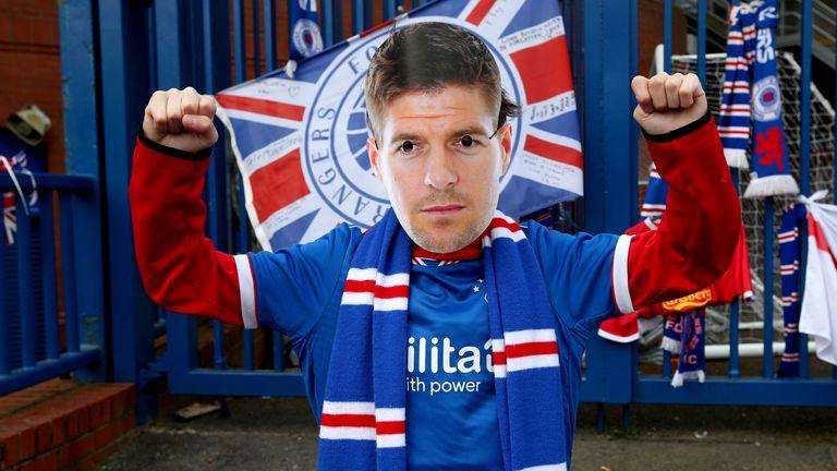 A Rangers fan celebrates the title win wearing a Steven Gerrard mask outside the Ibrox Stadium
