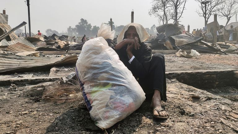 A Rohingya woman sits on the ground with her belongings after her shelter was burned down