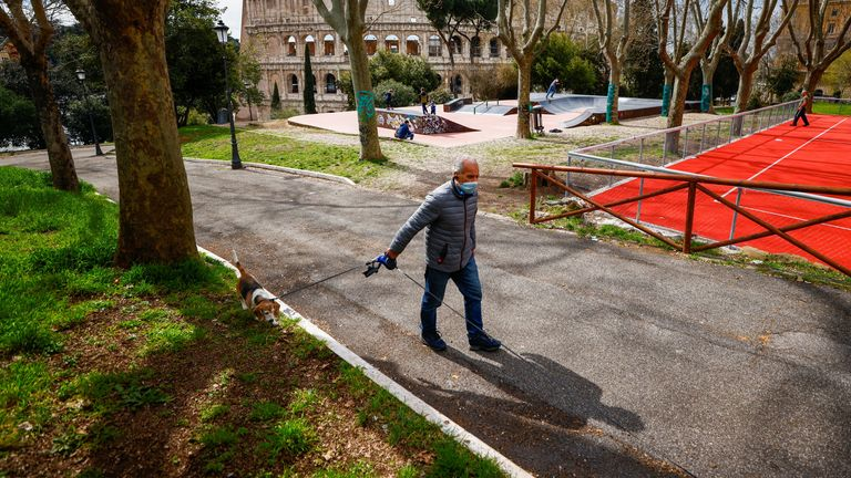 A man walks his dog near the Colosseum on the second day of lockdown, as the country struggles to reduce the coronavirus disease (COVID-19) infections, in Rome, Italy, March 16, 2021. REUTERS/Guglielmo Mangiapane
