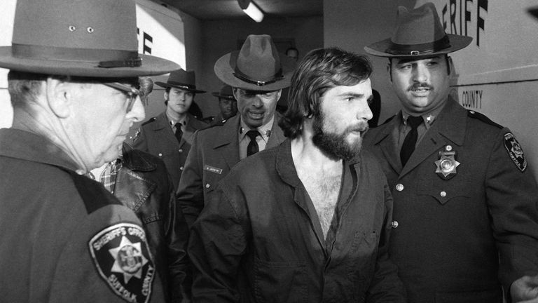 Ronald DeFeo Jr., center, leaves Suffolk County district court after a hearing, Nov. 15, 1974. DeFeo was ordered held without bail on one count of second-degree murder. He is accused of shooting his parents, two brothers and two sisters to death in their sleep on early Wednesday, November 13, at their home in Amityville, N.Y. (AP Photo/Richard Drew)