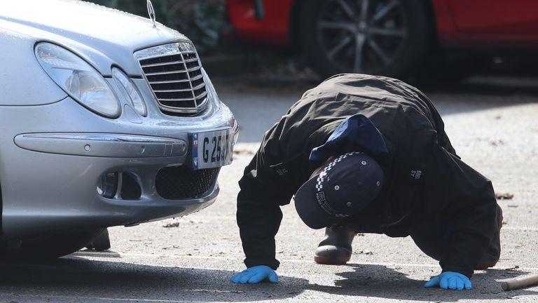 A police officer is seen looking under a car outside a Co-op in Sandwich
