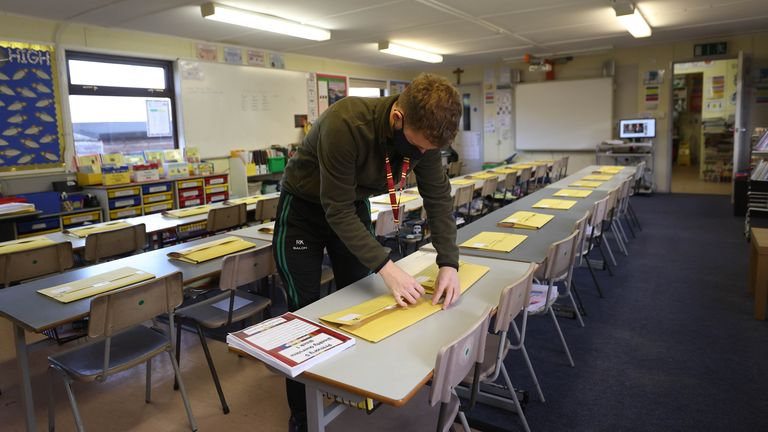 A primary school teacher lays out learning packs