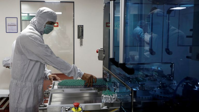 An employee in personal protective equipment (PPE) removes vials of AstraZeneca's COVISHIELD, coronavirus disease (COVID-19) vaccine from a visual inspection machine inside a lab at Serum Institute of India, in Pune, India, November 30, 2020. Picture taken November 30, 2020. REUTERS/Francis Mascarenhas/File Photo