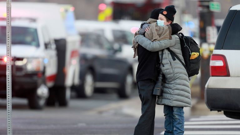Women hug on the corner of Broadway and Table Mesa Drive near a King Soopers grocery store where a shooting took place Monday. Pic: AP