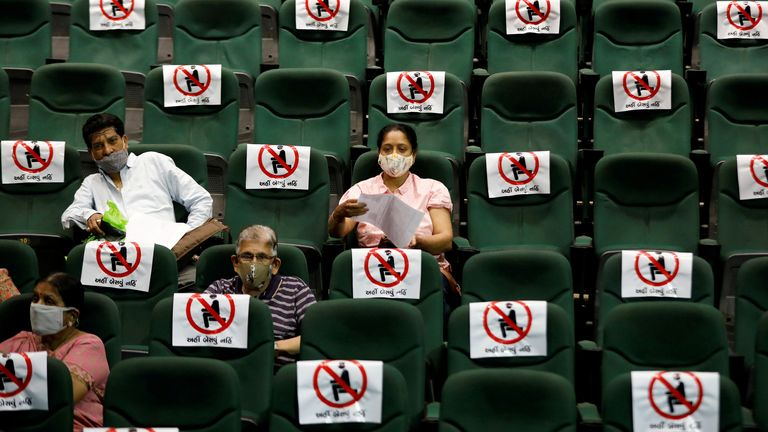 People sit under observation after receiving vaccine manufactured by Serum Institute of India, at a temporary vaccination centre in Ahmedabad