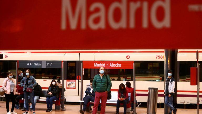 Commuters wear protective face masks wait on a platform at Atocha train station in Madrid