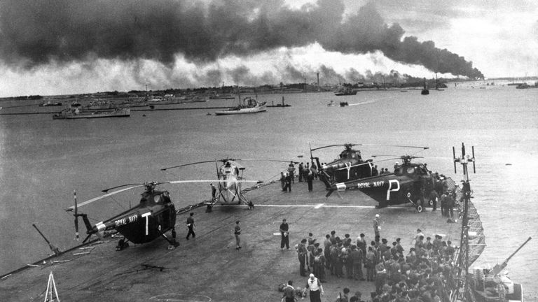 Troops and helicopters on deck of one of the first Royal Navy ships to enter Port Said, Egypt, which is seen shrouded in smoke and fire after its capture. 11/11/1956