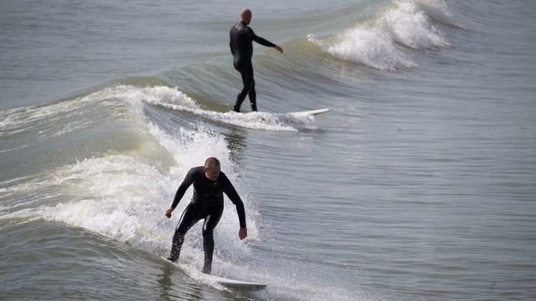 A person surfs a wave in the sea off of Bournemouth beach in Dorset. Picture date: Tuesday March 30, 2021. Temperatures in parts of the UK are expected to be significantly warmer this week as families and friends are reunited and sporting activities are allowed to resume in England.