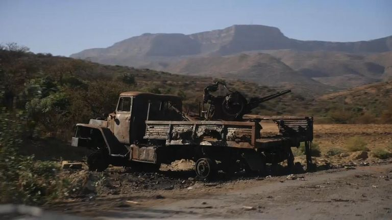 Burnt out trucks and military equipment are strewn on the roadside