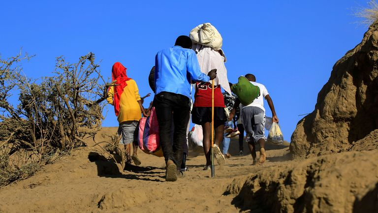 Ethiopians, who fled the ongoing fighting in Tigray region, carry their belongings after crossing the Setit River on the Sudan-Ethiopia border