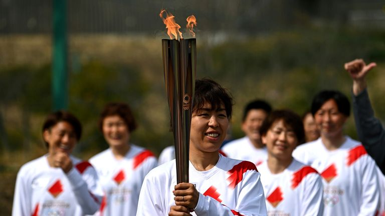 Japanese torchbearer Azusa Iwashimizu, a member of the Japan women's national football team, arrives at a torch 'kiss point' to pass on the flame during the torch relay