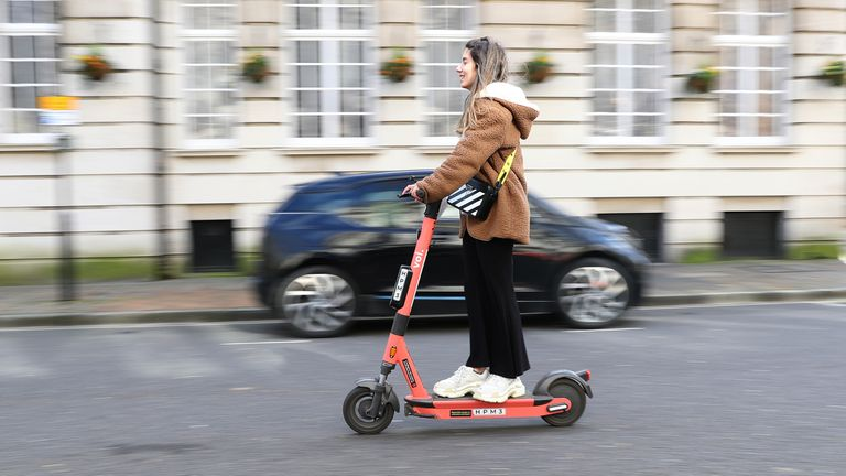 A woman rides a Voi rental e-scooter near the Guildhall in Portsmouth
