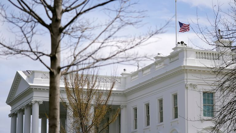 An American flag flies at half-staff above the White House in Washington, Tuesday, March 23, 2021. (AP Photo/Patrick Semansky)